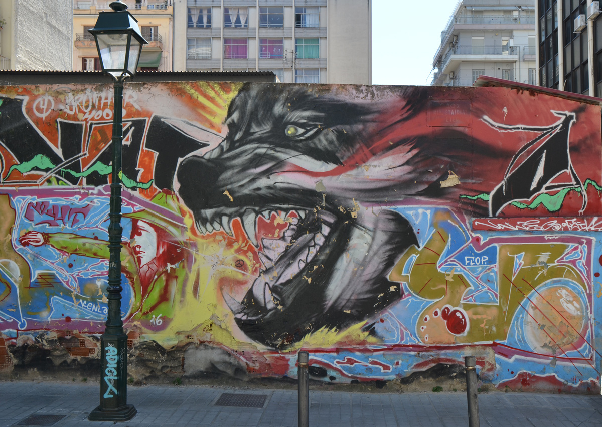 mural of a very large wolf, or dog, head with open mouth and large sharp teeth showing, chasing a man dressed in green, looks like the man is almost in the dogs mouth, small enough to fit whole man in the mouth