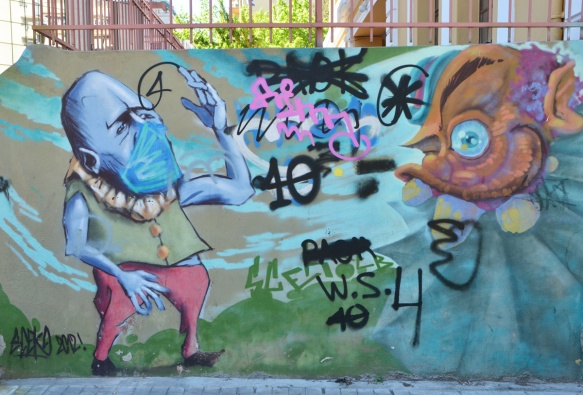 street art, short little purple man with oversized head, fabric mask over his nose and mouth, one arm up raised. on the other side of the mural is a creature with large eye and three monstrous teeth