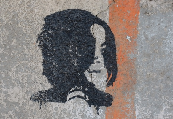 black stencil of Michael Jackson in profile on a concrete wall with an orange stripe painted on it