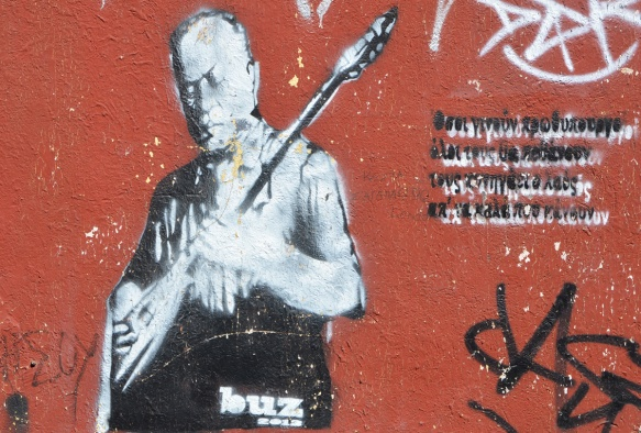 street art painting in black and white on a red wall of a musician, signature is buz 2012