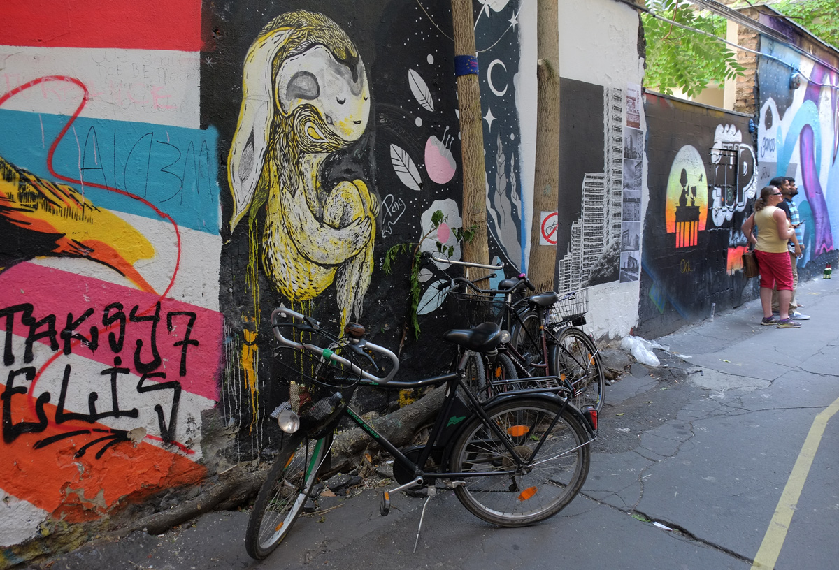 bike parked in front of a mural of a yellow human like creature with knees tucked up, people in the background looking at the street art