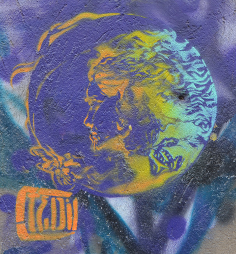 small street art painting, purple, circle shape with woman's profile in it, in light blues and oranges