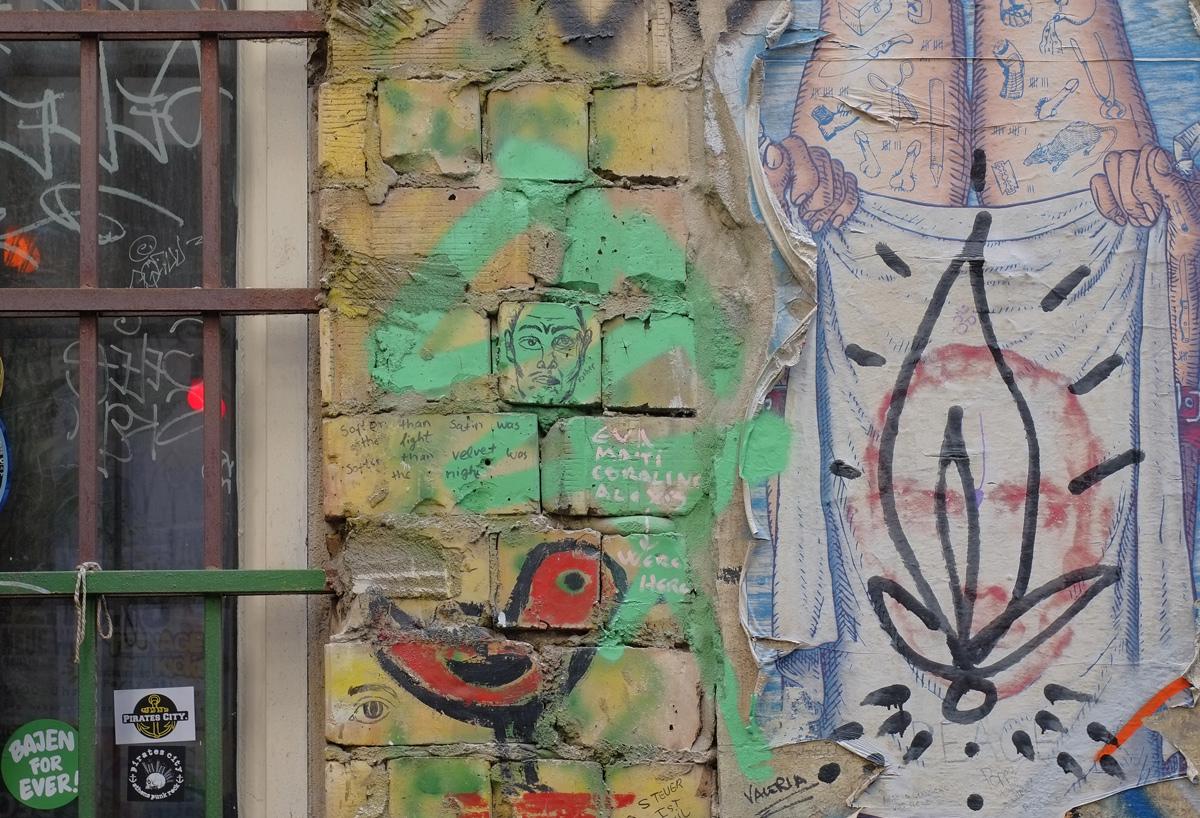 red bird graffiti, green with man's face, brick wall