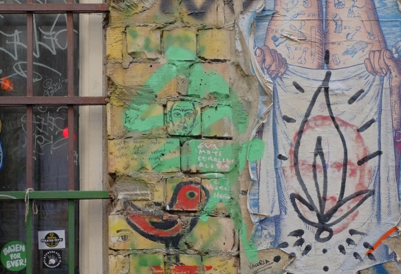 red bird graffiti, green with man's face, brick wall