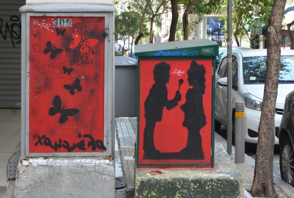 two metal boxes on the street with stencil graffiti, both with red background, one has many black butterflies and the other has a boy giving a flower to a girl, in silhouette