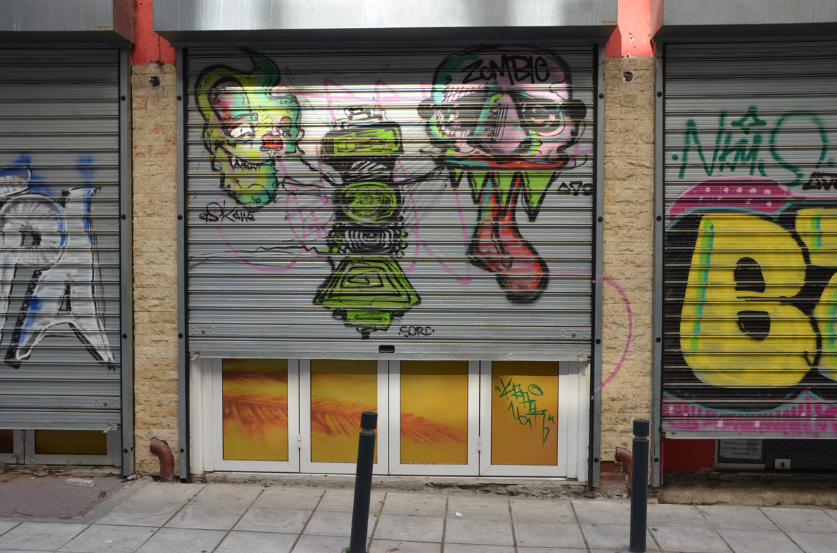 three ugly creatures drawn and painted on a metal door
