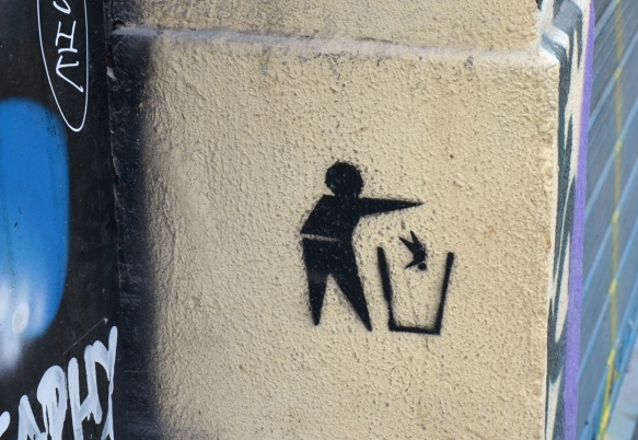 small black stencil of a person throwing a smaller person into a garbage can