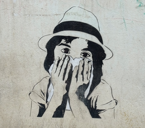 stencil of a young girl's head, shoulders and arms, wearing a hat, holding a piece of fabric over her mouth and nose