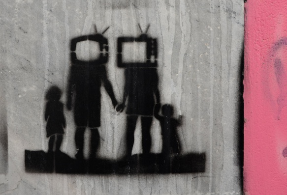 little black stencil of a family, parents have televisions for heads, standing in a row, all holding hands. seen in Athens Greece