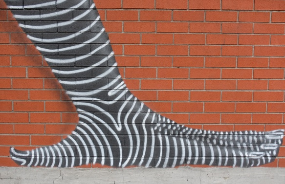 part of a larger mural, a black and white striped hand in on the ground, supporting two upside down figures