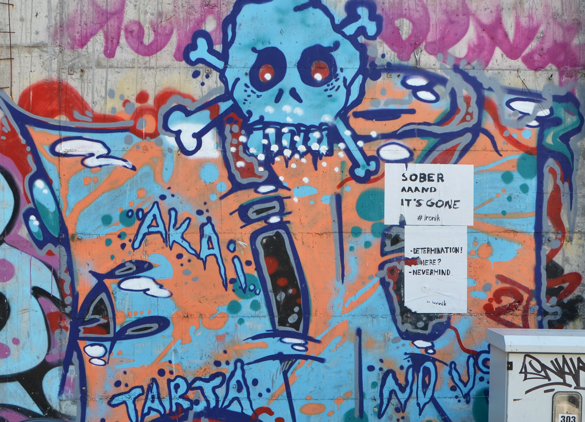 Street art and graffiti on a wall including a blue skull. Two white posters have been pasted on top, both by ironik. Words in English. One says