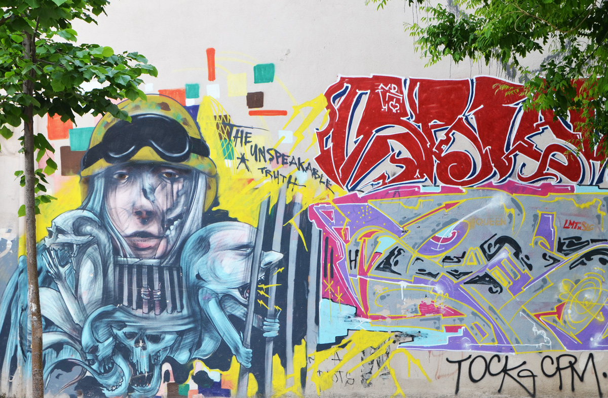 graffiti on a grey wall, a tree growing in front of it, a man in armour and old fashioned aviation goggles on his forehead, holding a creature with human like face and arms trying to break out from behind bars