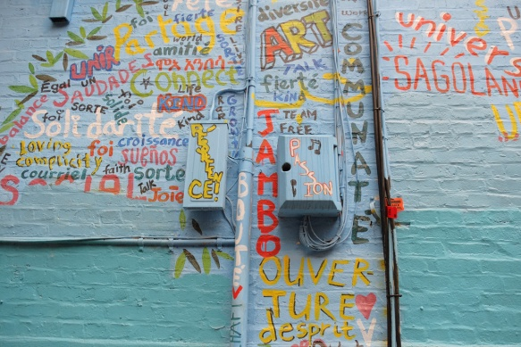 close up of part of street art mural in an alley, shape of a tree but filled in with words in different colours, words shuch as passion, communate, respect, fierte, English, French and Spanish words.