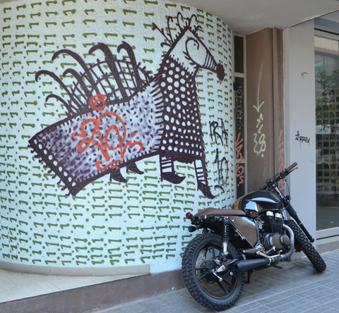 drawing of a horse with its back covered with a blanket, on a wall covered with small green horizontal lines, a motorbike is parked in front of it.