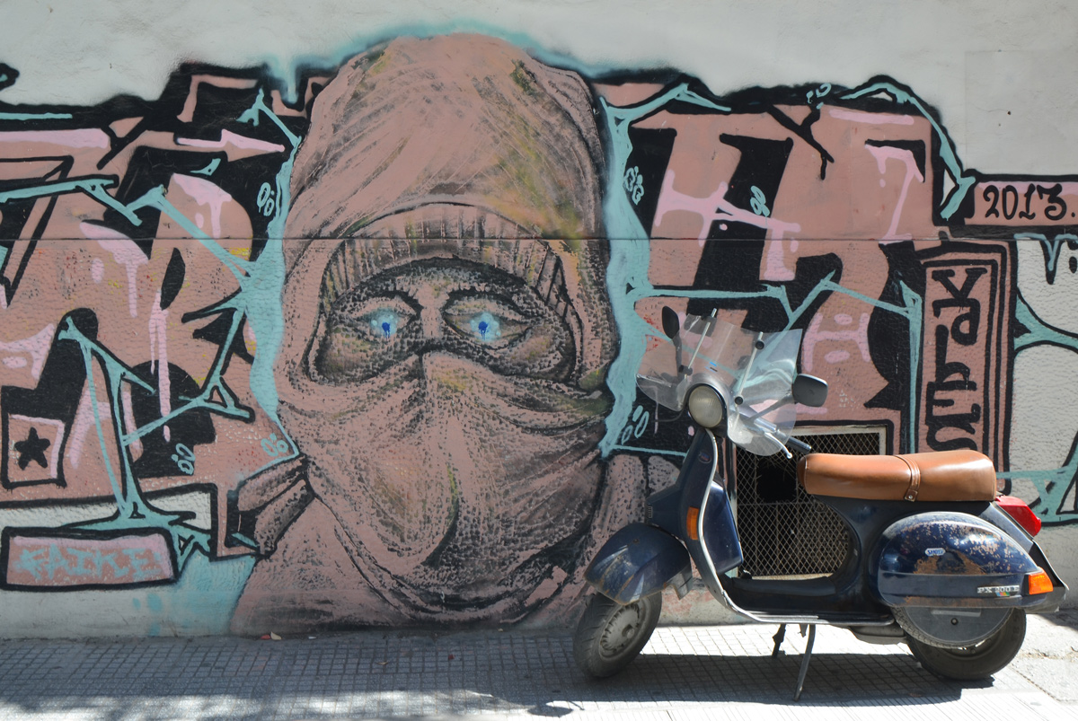 motorbike parked in front of a mural of a person with head covering and veil