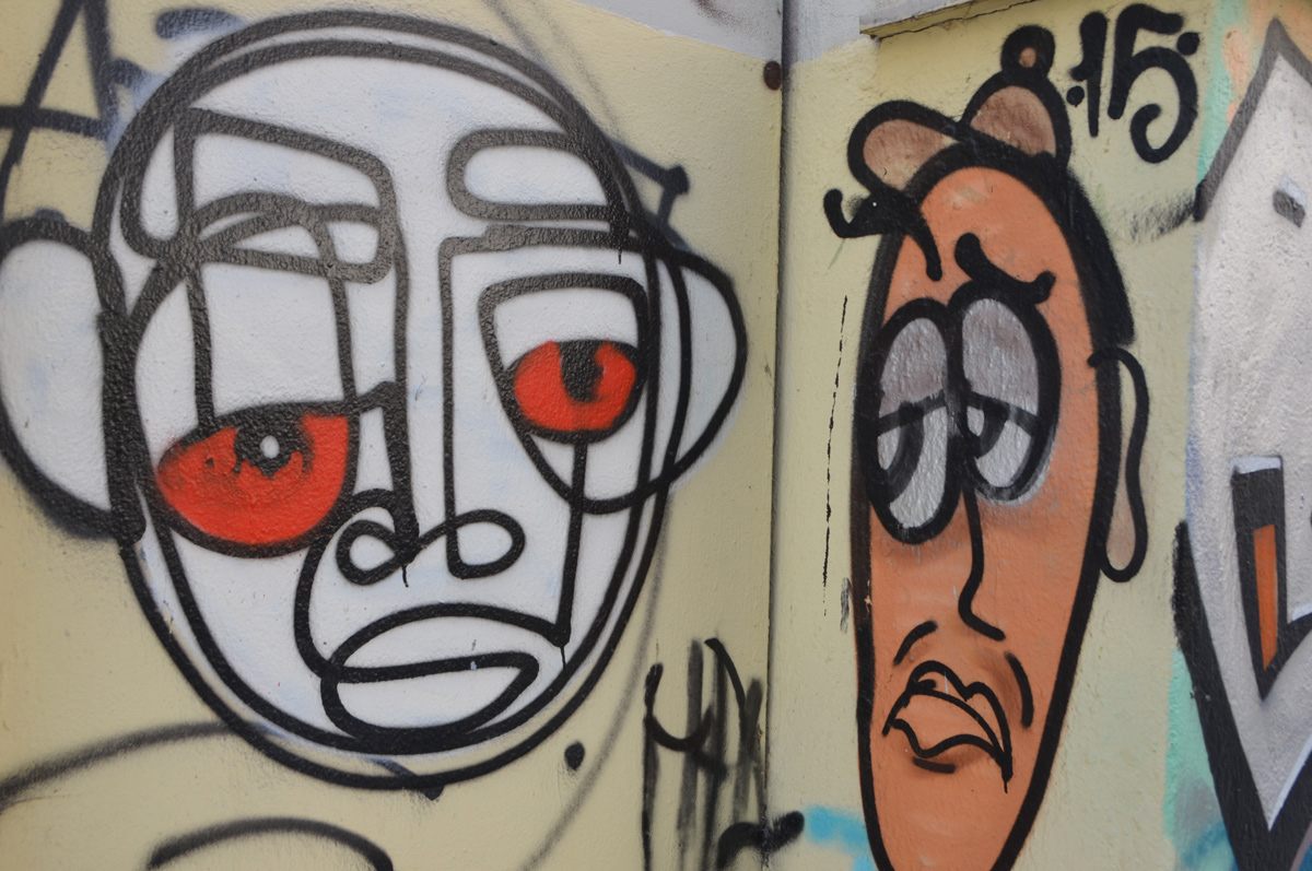 two street art faces, one white and one orange, both with lines drawn in black