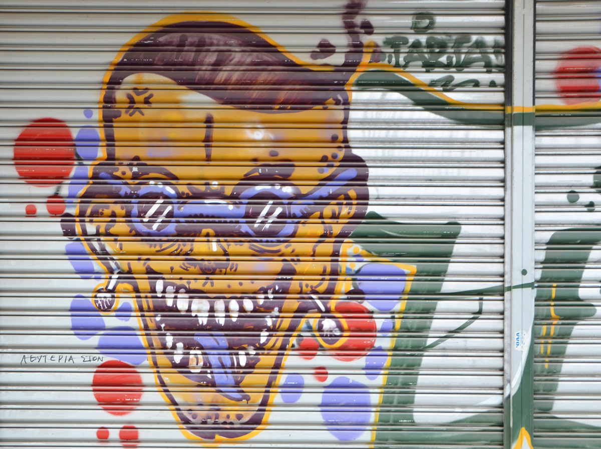 a large face painted on a garage door, yellow skin, purple sunglasses and purple tongue
