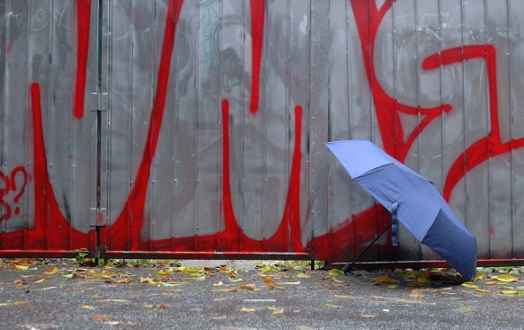 a blue umbrella beside a fence with large grey and red text graffiti, wet day, autumn, leaves on the ground,