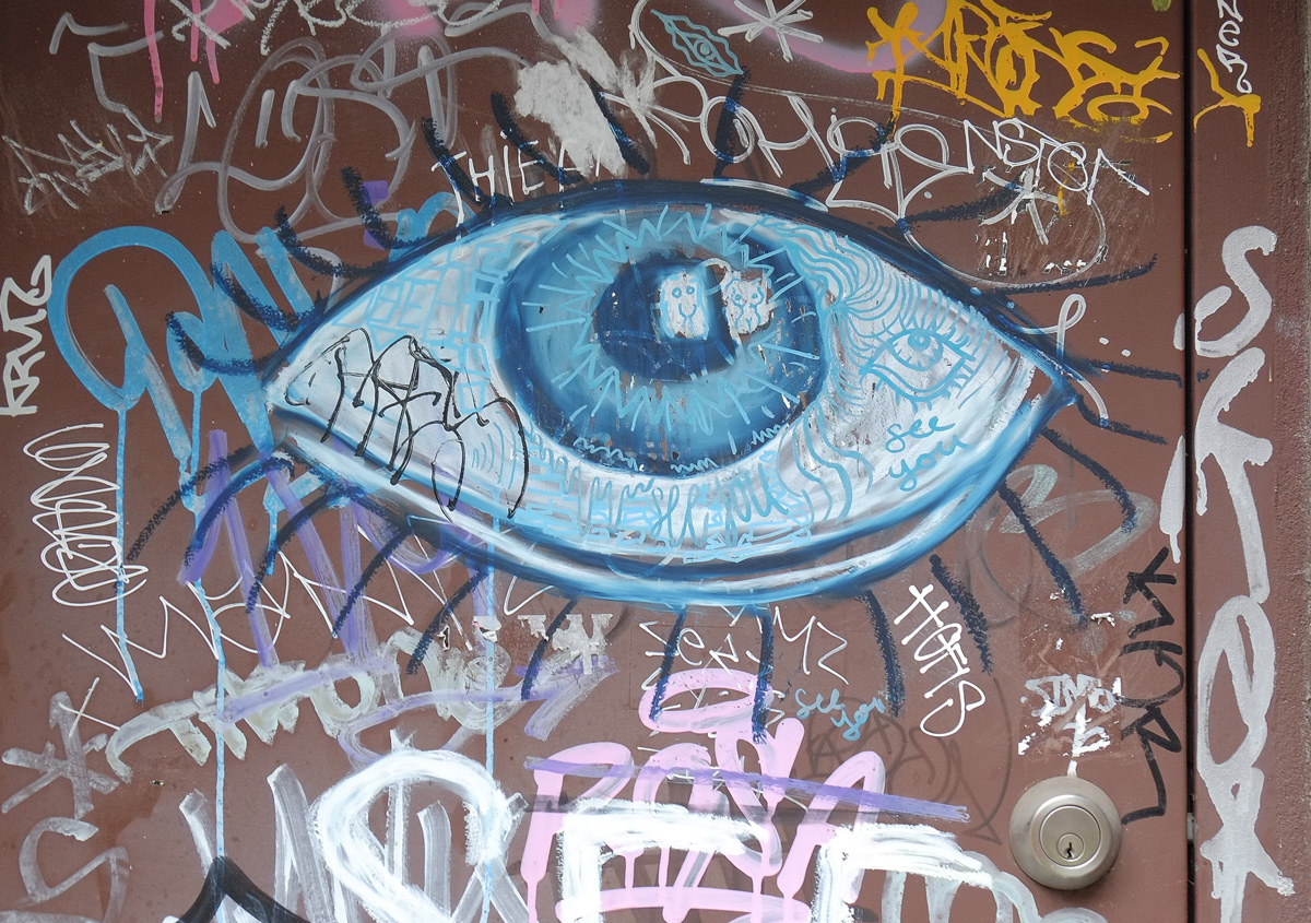 a bit blue eye painted on a brown door, with lots of graffiti around it.