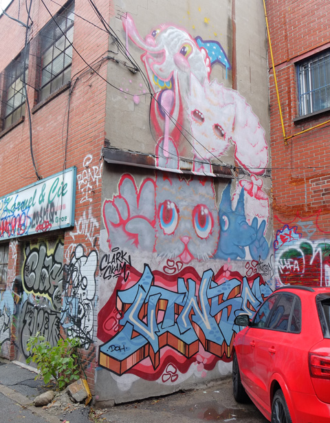 a mural of large pink animals has been tagged over on the bottom part