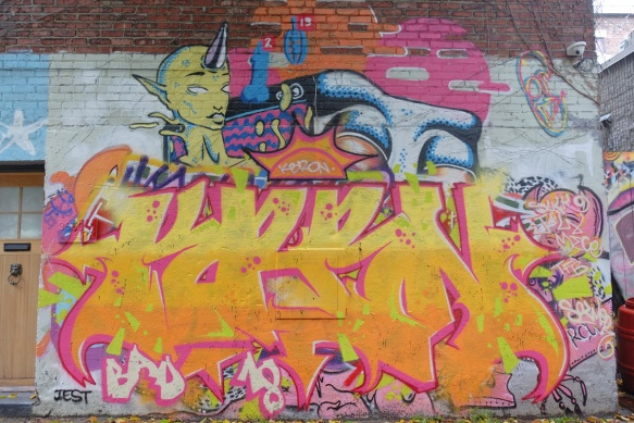 a large mural with a bright yellow and pink tag on the bottom of it,