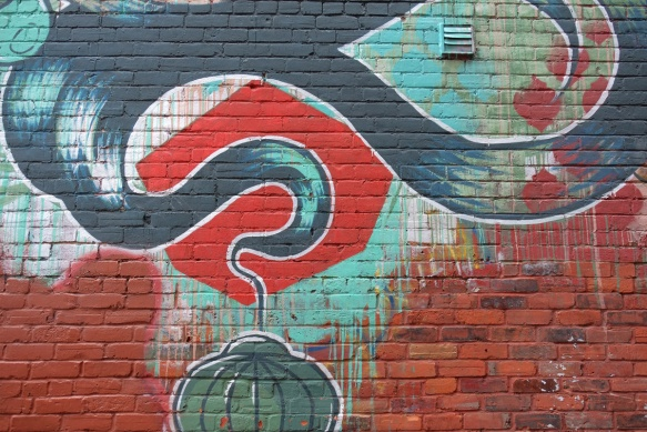small part of a large mural on a brick wall in an alley, red and green,