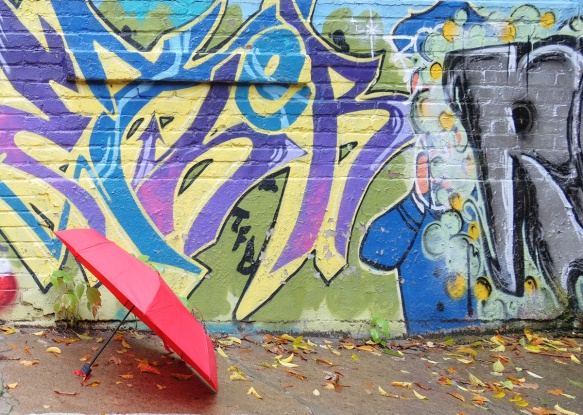a red umbrella sits on the ground beside a mural