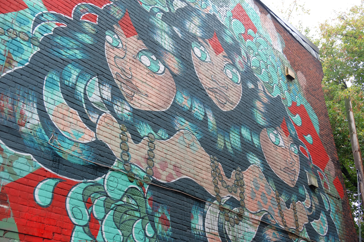 large mural on the side of the building, in greens on red background, three women with dark gren hair and bright green eyes