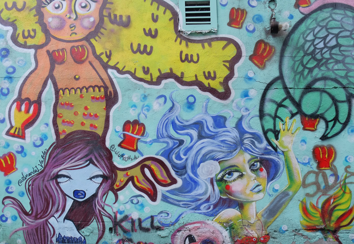 a mural with three different mermaids by three different artists