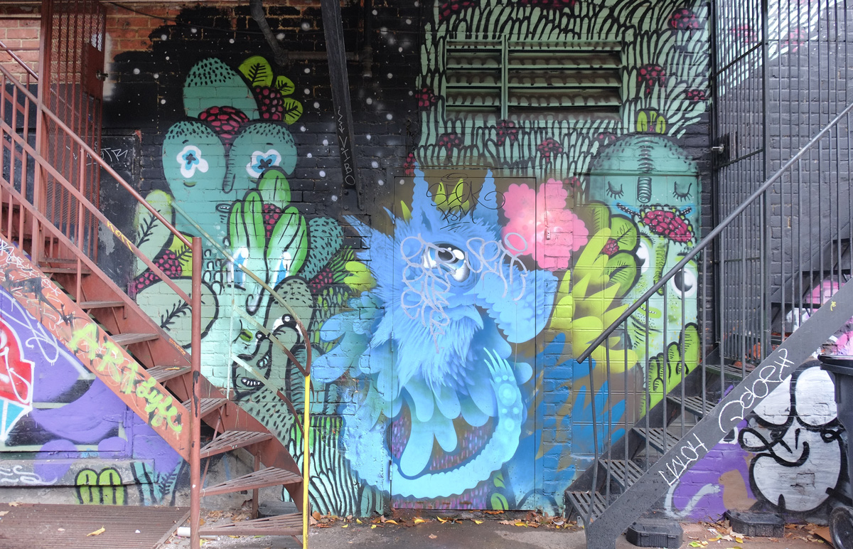 street art by wax head by two exterior metal staircases in a montreal alley, green and blue figures