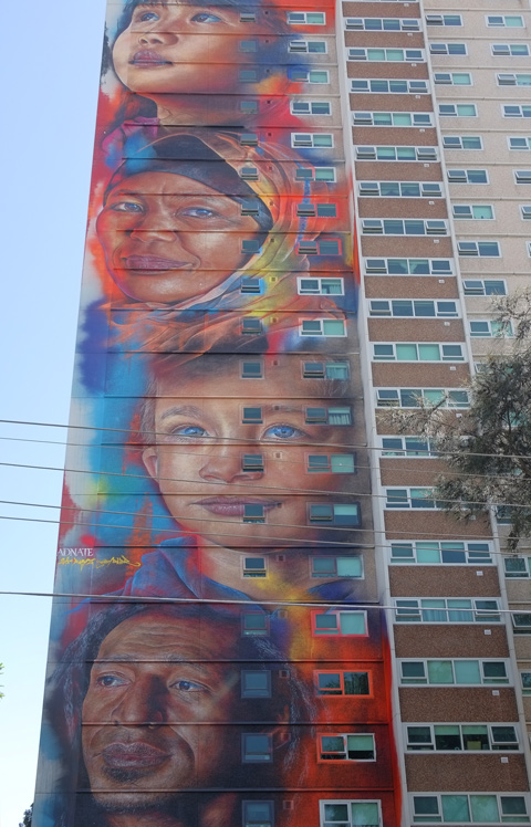 adnate faces, four, on a 20 storey high apartment building