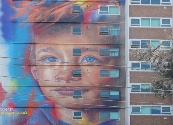 young boy's face in a mural by adnate