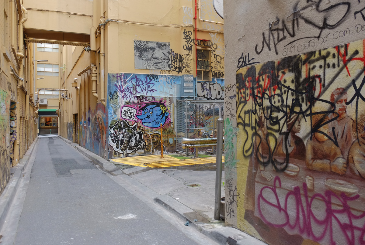 graffiti and street art in an alley, pale yellow walls