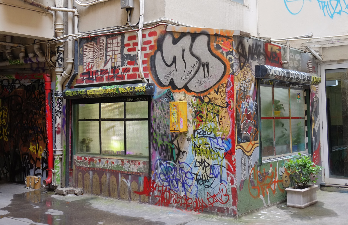 two windows in a small building in a lane, surrounding the windows is street art like a window box, awning, and then the wall space between the windows is decorated too