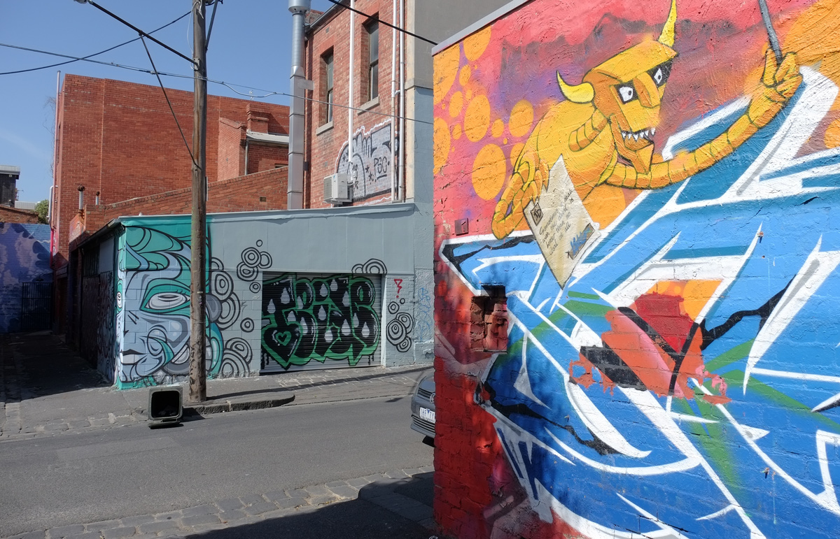 devil mural on the right, then looking across the street to another wall and garage door on Perry Street in Collingwood, that is painted with street art
