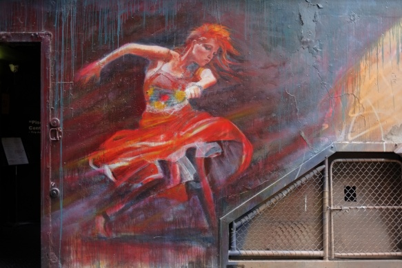 adnate maural of a woman dancing, wearing a red skirt and with red hair, swirling skirt, arm up as she dances
