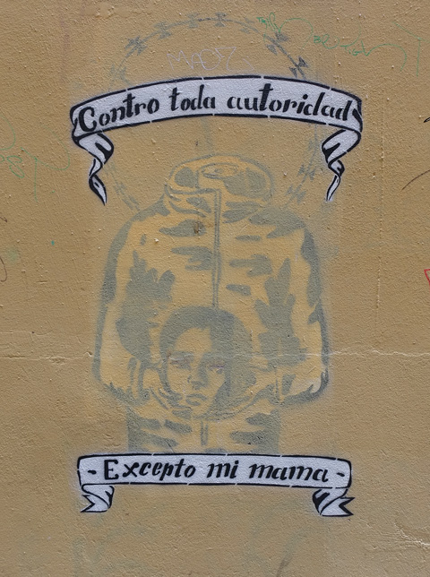words on top and below a headless figure holding the head of a woman in its hands, words say contro toda autoridad excepto mi mama which is Spanish for I defy all authority except my mother