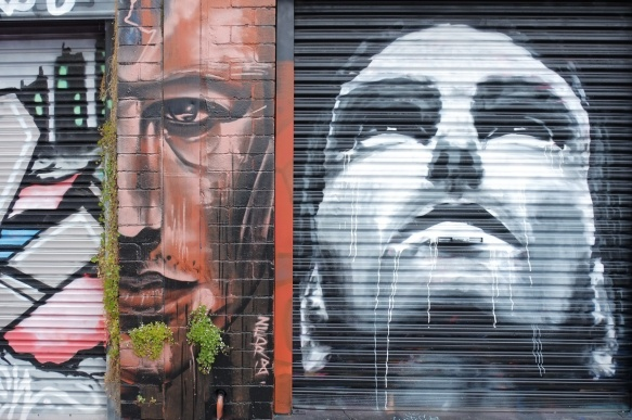 two faces painted in Artists Lane in Windsor Melbourne, two male faces, one in black and white and the other in shades of brown. The black and white one is looking up, the brown one is only half a face (divided down the middle of the face, on eye, half a nose, and half a mouth.
