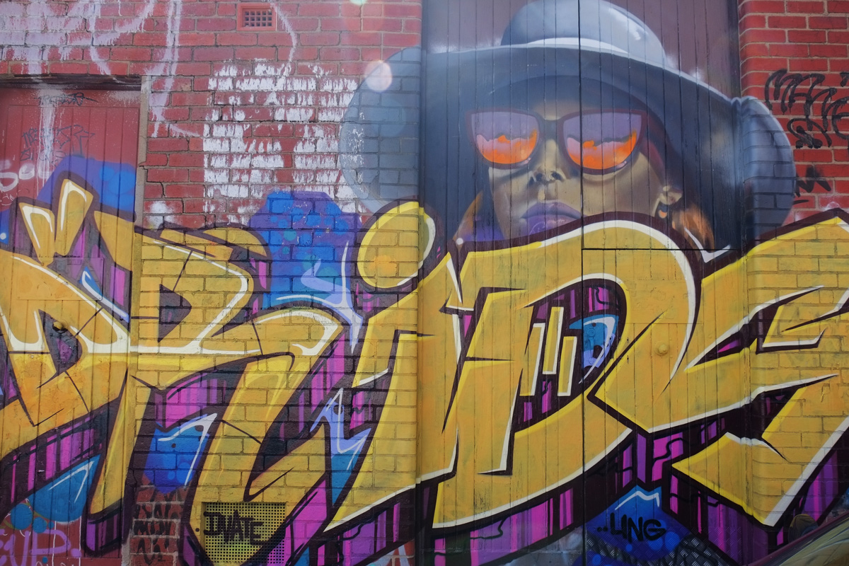 gold letter text street art with a picture of a woman in broad rimmed hat and purple and orange sunglasses