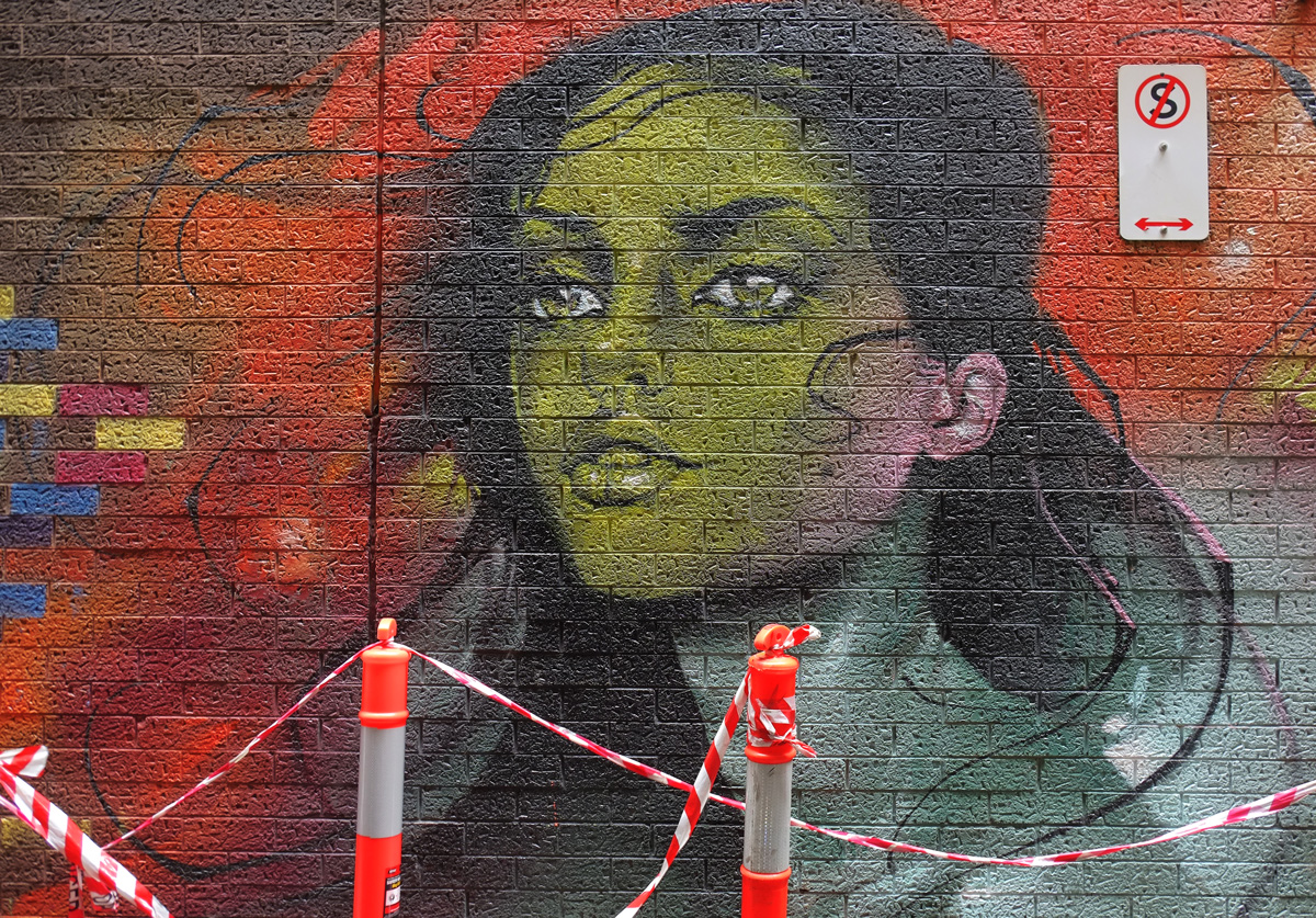 orange and white traffic markers in front of a mural in a lane, on a brick wall, of a woman's face and head, green skin on face, blue skin on neck, long black hair, blue eyes, 3/4 profile position