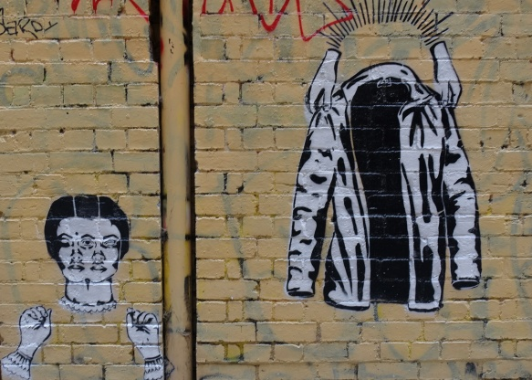 two black and white pasteups on a wall. on the right is a pair of white hands holding up an open jacket and on the left is a woman's head with two pairs of eyes, and a pair of hands below the head