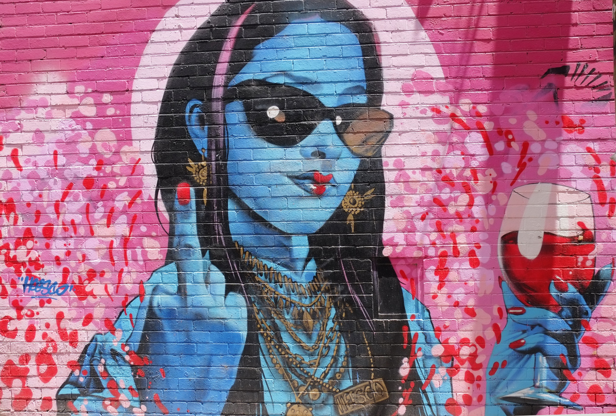 mural of a large than life blue woman, (head and upper body), long black hair, sunglasses, red lips, lots of necklaces, glass of red wine in one hand, red nail polish, giving the finger with the other hand, pink background, by heesco,