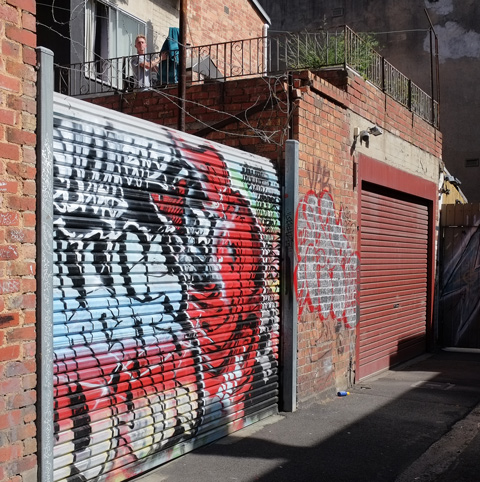 man on a balcony above a garage is looking down into the alley, another garage door has street art sprayed onto it