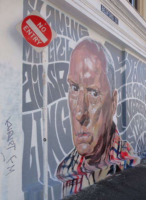 large painting of a man's head on the exterior wall, surrounded by grey words