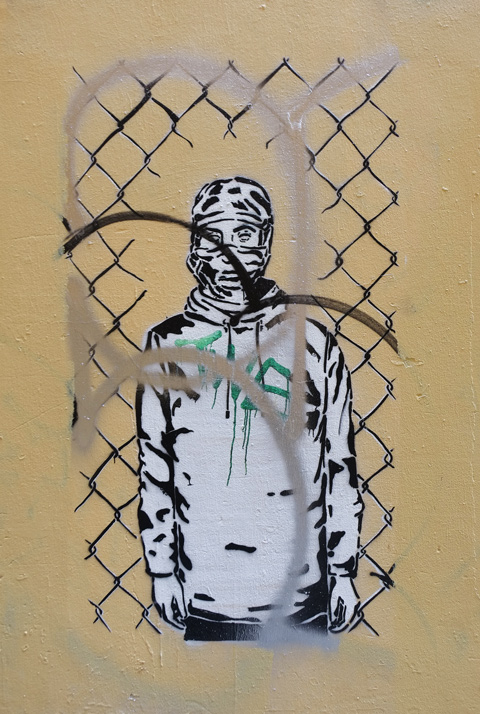 black and white pasteup of a person in a hoodie standing behind a chain link fence with a hole in it.