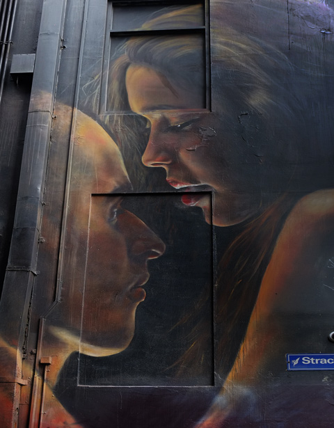 large mral by adnate of a couple kissing, the woman's head is above the man's head and she is looking down at him as her mouth comes close to his nose.