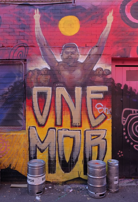 street art painting of a man topless with arms over head in victory, with text underneath that says one mob