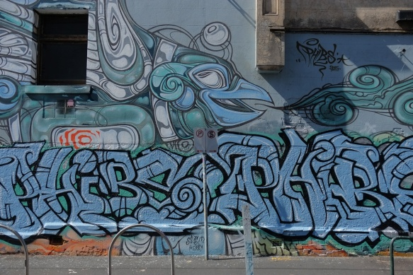 upper part is part of a mural by phibs in blues and greys of fish, drawn with lines and circles, the bottom part is a large blue tag.