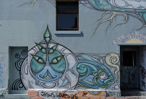 a street art liion in blues, stylized, also a fish, on a wall under a window and beside a door, by phibs in 2015, on a street in Melbourne Australia