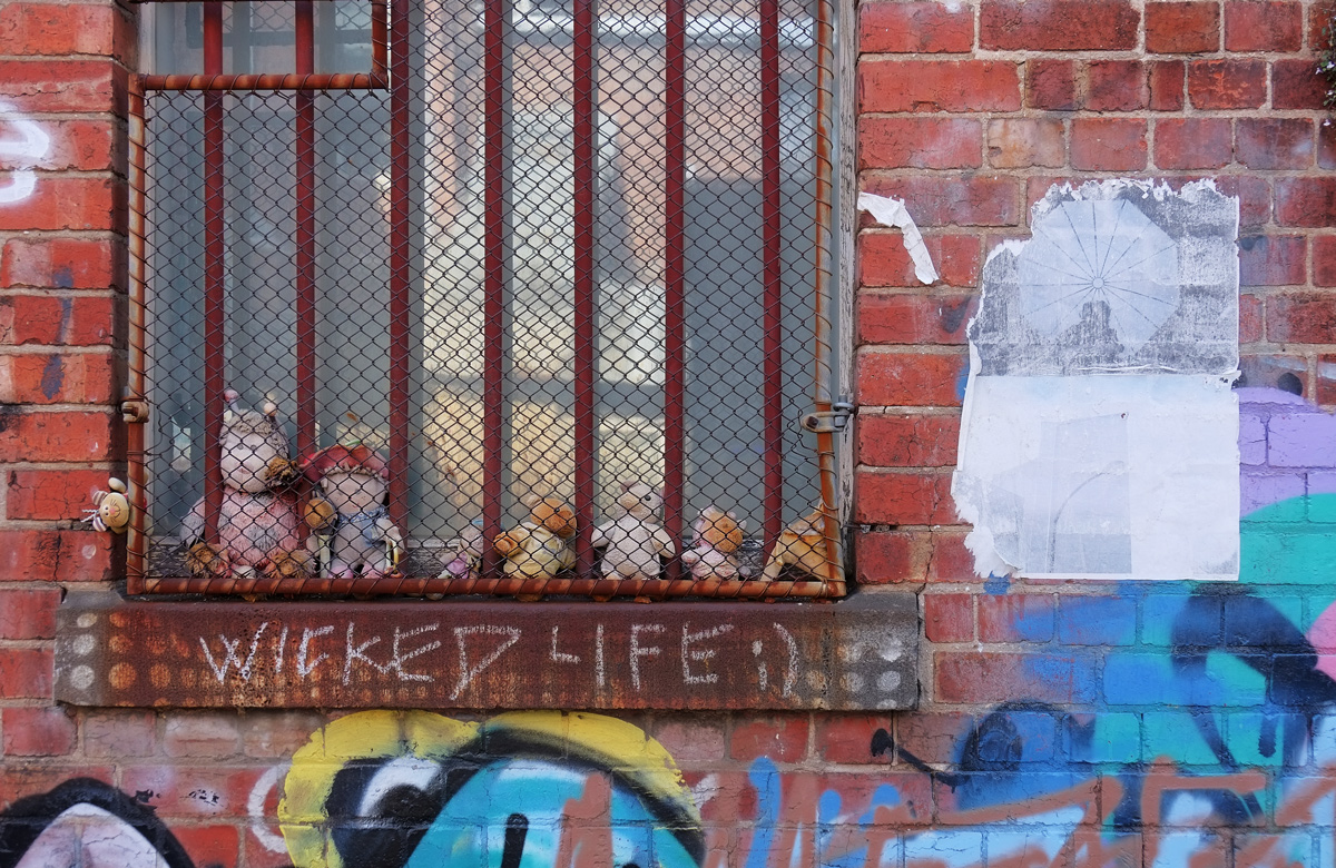 a row of stuffies behind a rusty metal grille in front of a window.